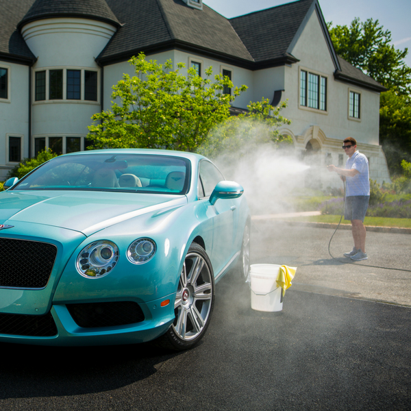 Man washing a blue Bentley with Stoner Car Care products