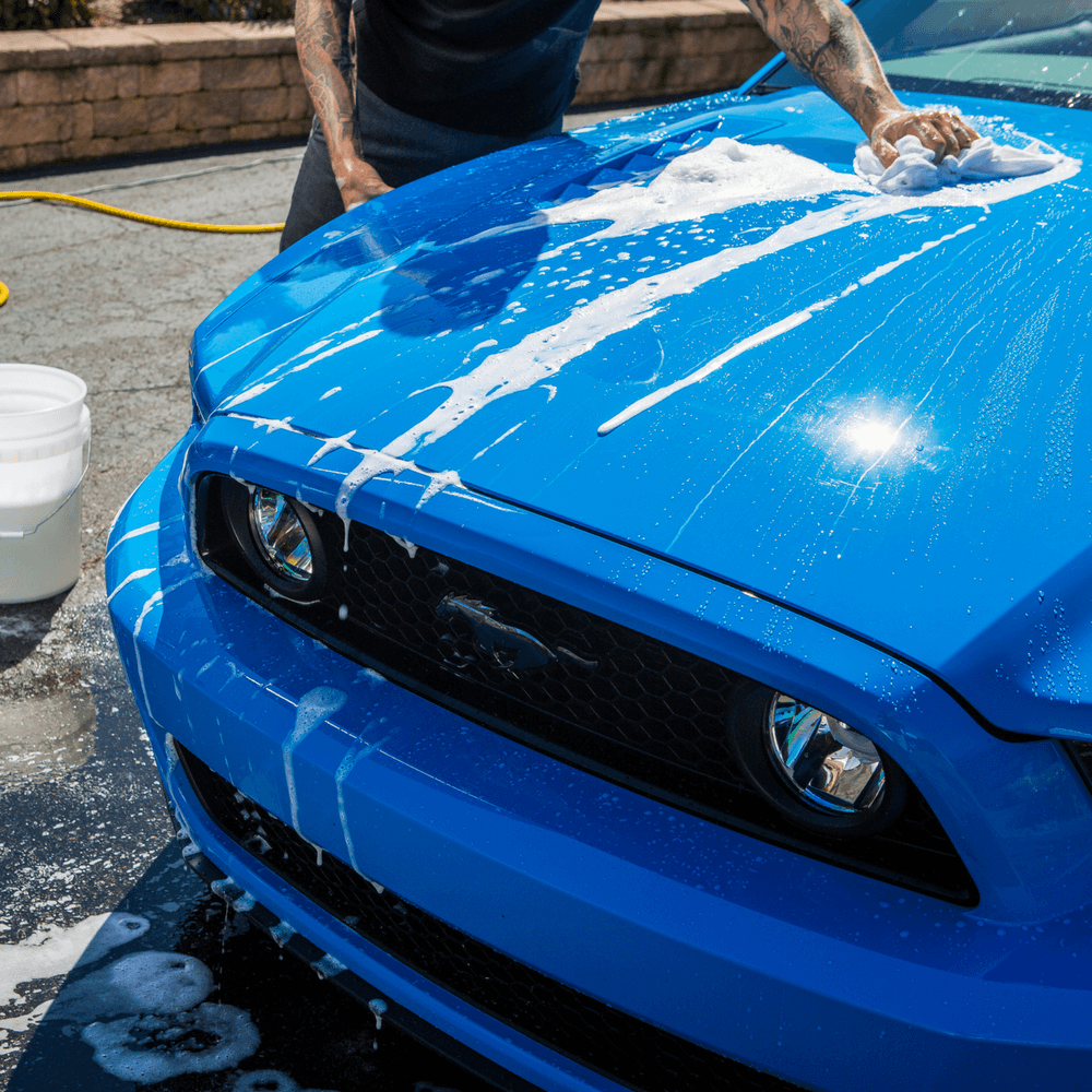 Man cleaning blue Ford Mustang with Stoner Car Care Wash and Wax product