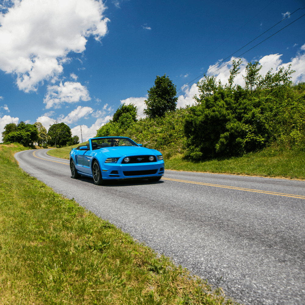 Blue Ford Mustang convertible driving on country road